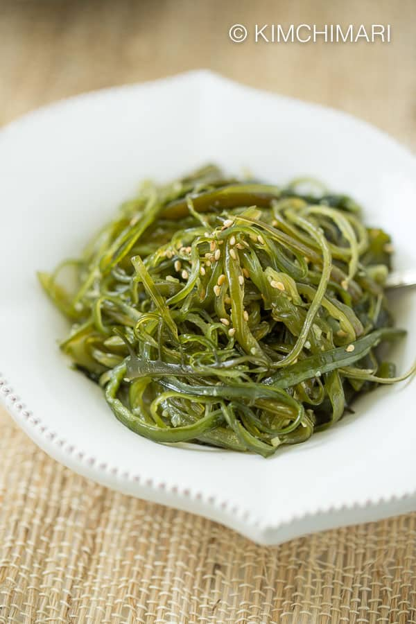 Sauteed seaweed stems in white bowl on straw placemat