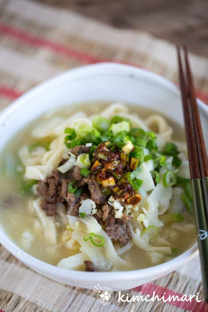 Kalguksu in large bowl with all toppings and wooden chopsticks